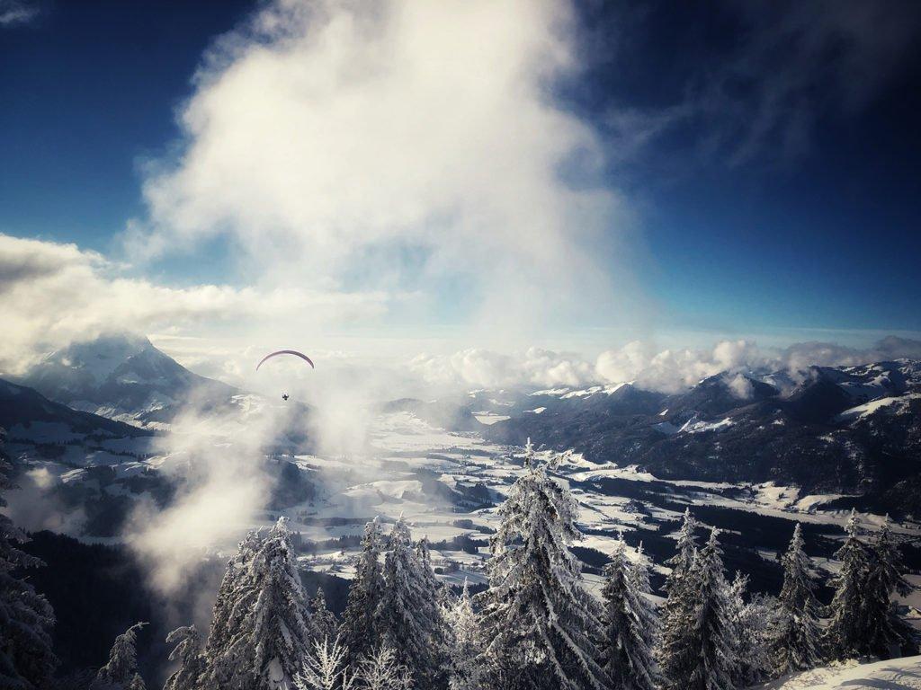 Blick von einer Winterlandschaft auf einem Berg in den Alpen Richtung Tal. Ein Paragleiter ist zu sehen, der scheinbar über den Wolken schwebt.