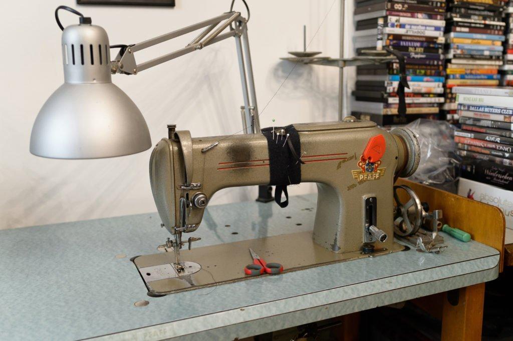 In Christian Kratzert seinem Atelier. Zu sehen ist eine Nähmaschine, mit der er arbeitet. Im Hintergund ein Stapel an DVDs, die ihm auch zur Inspiration dienen.