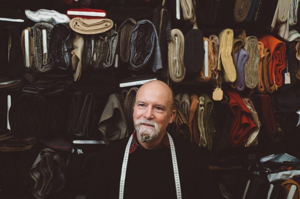 Christian Kratzert in seinem Atelier vor verschiedenen Stoffen, die er lagert.